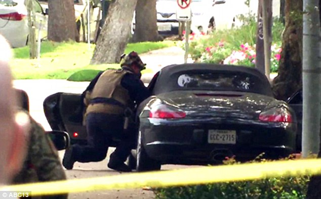 Police search a Porsche Boxster registered to lawyer Nathan DeSai near the scene where sources say he shot nine people in southwest Houston
